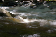 Churning water. Rapids at the base of some falls on the Red river in Quebec royalty free stock photo