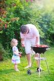 Churrasco do pai e da filha no jardim Fotografia de Stock Royalty Free