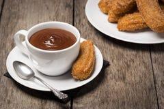 Churros用在木表上的巧克力 免版税库存照片