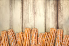 Churros arranged in row. On wooden background stock photo