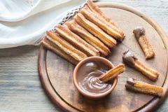 Churros - berömd spansk efterrätt med chokladsås Arkivfoto