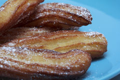 Churros on blue plate Royalty Free Stock Photo
