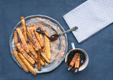 Churros with chocolate sauce on a metal plate over a linen backg Stock Photos