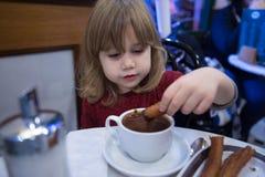 Churros de mergulho da criança feliz no chocolate Fotografia de Stock Royalty Free