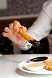 Churros espagnols de plongement d'une main pour chauffer la crème au chocolat foncée Photo libre de droits