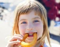Churros Essen des kleinen Mädchens der blauen Augen Lächeln lizenzfreie stockfotografie