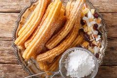 Churros is gouden en knapperige gebraden die gebakjes met het close-up van het suikerpoeder op een plaat worden bestrooid horizon stock afbeeldingen