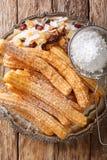 Churros is gouden en knapperige gebraden die gebakjes met het close-up van het suikerpoeder op een plaat worden bestrooid Vertica stock foto