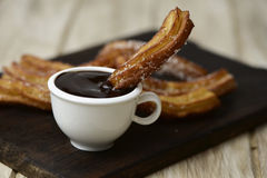 Churros lurar choklad, ett typisk spanskt sött mellanmål Arkivfoton