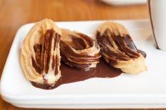 Churros med smältt choklad Arkivbild