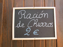 Churros ration in blackboard. Black placard spanish white handwritten in wall with typical menu food dishes like churros ration in Spain restaurant Royalty Free Stock Images
