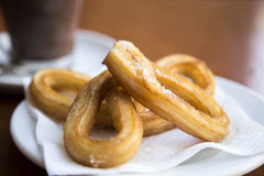 Churros. Spanish Churros with hot chocolate in background Royalty Free Stock Photography