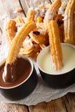 Churros tradicionais com close-up do chocolate quente e do leite condensado vertical imagens de stock royalty free