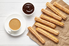 Churros traditional Spain street fast food baked sweet dough snack with chocolate and coffee. Rustic decorative parchment paper, white table background. Flat Royalty Free Stock Photo