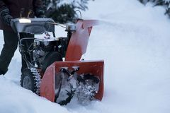 Chute and Auger - Snowblower at Work. A man operating a shiny new orange snowblower in deep snow Royalty Free Stock Image