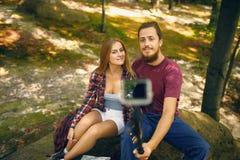 Chute dans des couples d'amour posant tout en tenant l'appareil-photo d'action Photographie stock libre de droits