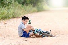 Chute de garçon de la bicyclette pendant le tour sur la route Photo stock