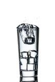 Chute de glaçon dans le verre de l'eau à la cause une éclaboussure photos libres de droits