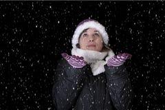 Chute de neige sur la jeune femme dans les wiinterclothes Images stock