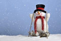 Chute de neige sur le bonhomme de neige mignon sur des skis Photographie stock libre de droits