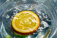 Chute orange de fruits tropicaux profondément sous l'eau avec une grande éclaboussure images libres de droits