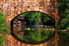 Chutes dans la réflexion au pont en pierre caché Photos libres de droits