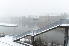 Chutes de neige au-dessus de la rivière principale dans Schweinfurt avec des escaliers d'un pont Photos stock