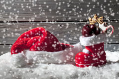 Chutes de neige avec le chapeau et la botte de Noël sur le tas de la neige sur le fond en bois Images stock