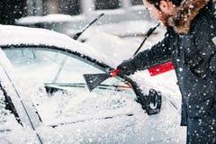 Chutes de neige d'hiver - véhicules de nettoyage de personnes Entretien automobile d'hiver avec le balai, la brosse et le grattoi photo libre de droits