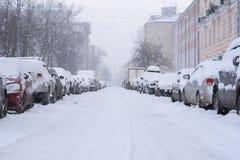 Chutes de neige dans la rue vide avec les voitures garées Images stock