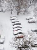 Chutes de neige dans la ville et voitures sur le stationnement Images stock