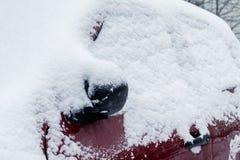 Chutes de neige dans la ville, une partie de la voiture couverte par la neige photos stock