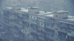 Chutes de neige derrière la fenêtre avec le fond brouillé des blocs de voisinage clips vidéos