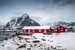 Chutes de neige sur la maison rouge avec le port en vallée sur l'océan arctique photos libres de droits