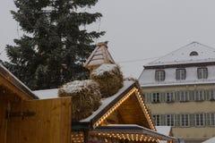 chutes de neige sur le marché de Noël avec les lampes et la décoration de lumières dedans photographie stock