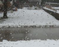 A chuva deixa cair na janela com fundo da neve e da rua fotos de stock