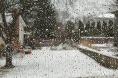 A chuva deixa cair na janela com paisagem nevado como o fundo foto de stock royalty free