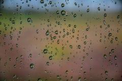 A chuva deixa cair na janela de carro com luz solar, vidro molhado, dia chuvoso fotografia de stock royalty free