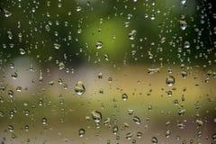 A chuva deixa cair na janela de carro com luz solar, vidro molhado, dia chuvoso fotos de stock royalty free