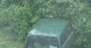 A chuva derrama no carro estacionado 4k video filme