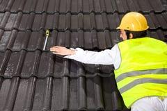 Trabalhador que encontra-se no telhado que tenta tomar a seu a fita Imagens de Stock