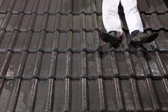 Trabalhador em telhas de telhado da fixação do telhado Imagens de Stock