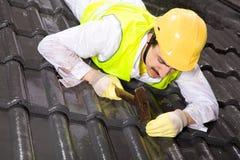 Trabalhador em telhas de telhado da fixação do telhado Fotografia de Stock Royalty Free