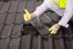 Trabalhador em telhas de telhado da fixação do telhado e em polegares da exibição acima Fotografia de Stock