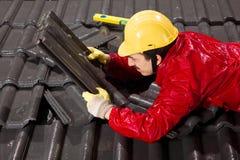 Trabalhador em telhas de telhado da fixação do telhado Imagem de Stock