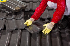 Trabalhador em telhas de telhado da fixação do telhado Fotos de Stock Royalty Free
