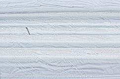 Chuva no plástico sobre a madeira serrada envolvida Imagens de Stock Royalty Free