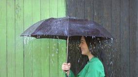 A chuva pesada derrama na menina protegida sob o guarda-chuva filme