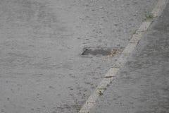 Chuva pesada do verão e o dreno obstruído fotos de stock