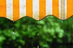 Chuva Toldo em um balcão e em gotas da água em um fundo colorido natural durante um dia de mola imagens de stock royalty free